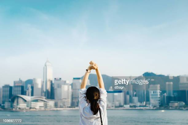 Rear view of woman traveller enjoying her time in Hong Kong, taking a deep breath with hands raised against Victoria Harbour and city skyline