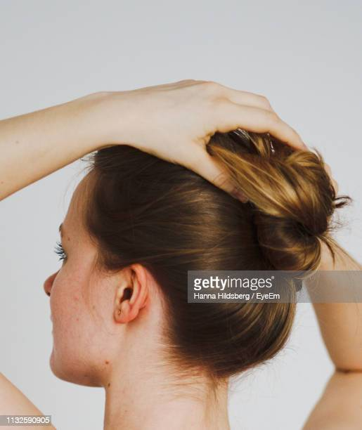 rear view of woman tying hair against white background - up do stock pictures, royalty-free photos & images
