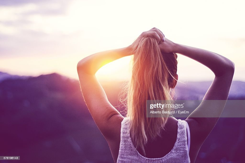 Rear View Of Woman Tying Ponytail Against Mountain During Sunset : Stock Photo
