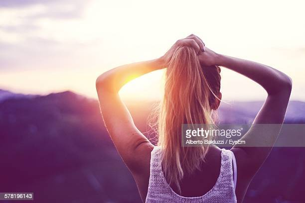 rear view of woman tying ponytail against mountain during sunset - lila stock-fotos und bilder