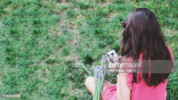 Rear View Of Woman Using Phone While Sitting On Field