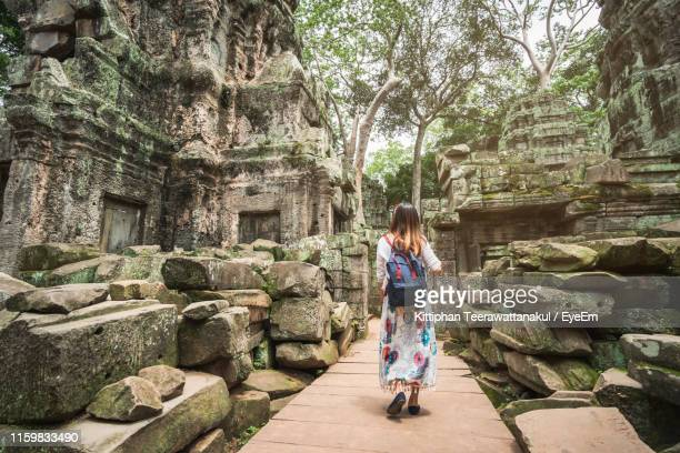 rear view of woman visiting old ancient temples - angkor wat stock pictures, royalty-free photos & images