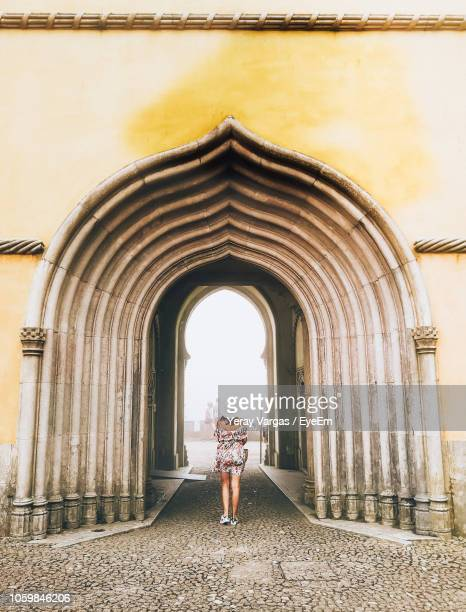 rear view of woman walking against arch - sintra stock pictures, royalty-free photos & images