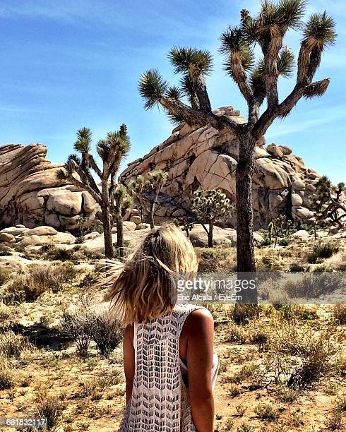 Rear View Of Woman Walking Against Joshua Tree On Sunny Day