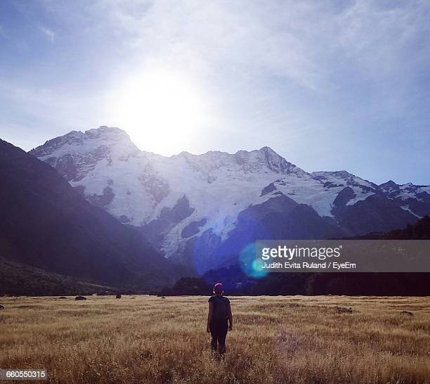 Rear View Of Woman Walking Against Mountains At Mt Cook National Park During Sunny Day