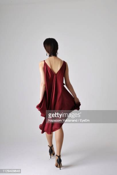 rear view of woman walking against white background - dress stock pictures, royalty-free photos & images