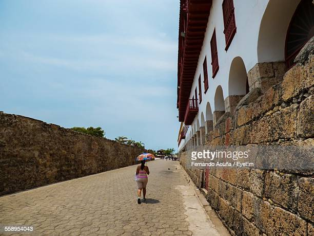 rear view of woman walking along wall - barranquilla stock photos and pictures