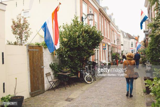 rear view of woman walking amidst dutch flags on buildings - haarlem stock photos and pictures