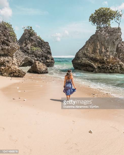 rear view of woman walking at beach against sky - indonesia stock pictures, royalty-free photos & images