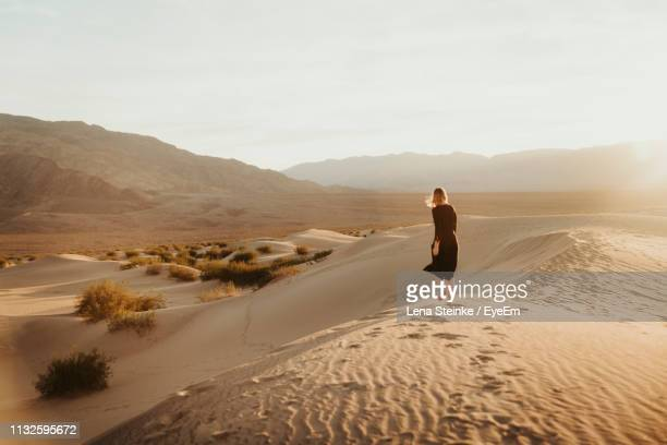 rear view of woman walking at desert against sky during sunset - great basin stock pictures, royalty-free photos & images