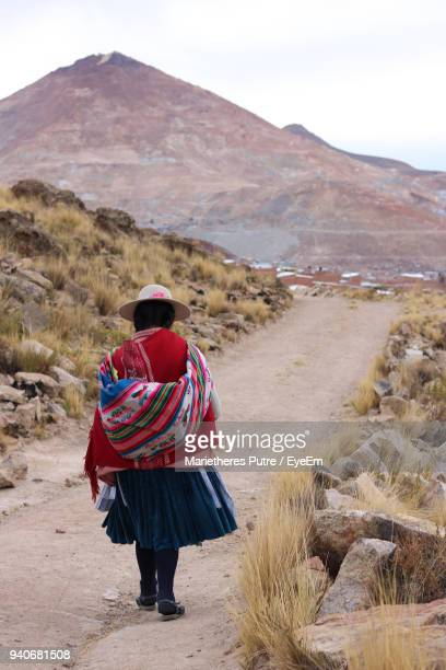 Rear View Of Woman Walking At Desert Against Sky