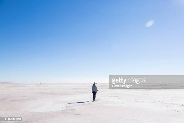 rear view of woman walking at great salt lake against blue sky during sunny day - bonneville salt flats stock pictures, royalty-free photos & images