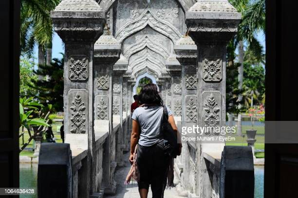 rear view of woman walking at ujung water palace - oppie muharti stock pictures, royalty-free photos & images