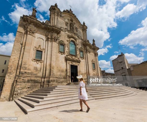 rear view of woman walking by church against cloudy sky - マテーラ ストックフォトと画像
