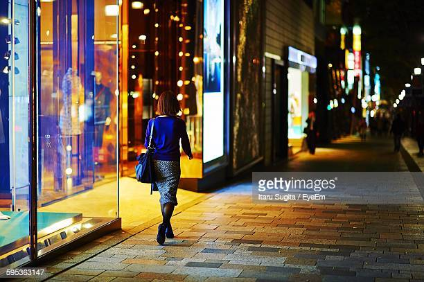 Rear View Of Woman Walking By Illuminated Store On Street At Night