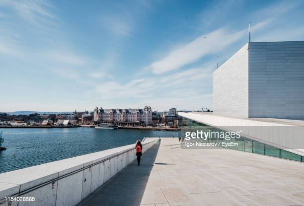 rear view of woman walking by river against sky in city - オスロ ストックフォトと画像