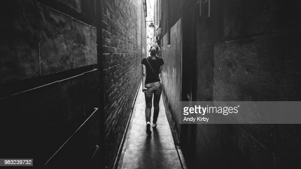 rear view of woman walking down narrow alley, bridges place, london, england, uk - narrow stock pictures, royalty-free photos & images
