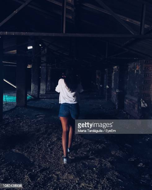 Rear View Of Woman Walking In Abandoned Building