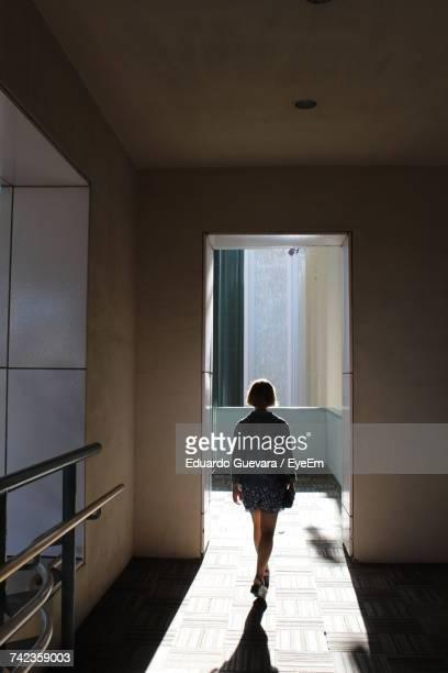 Rear View Of Woman Walking In Corridor