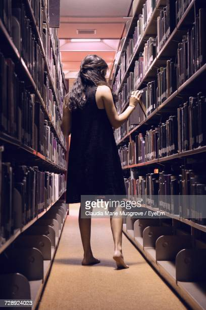 rear view of woman walking in library - claudia marie stock-fotos und bilder