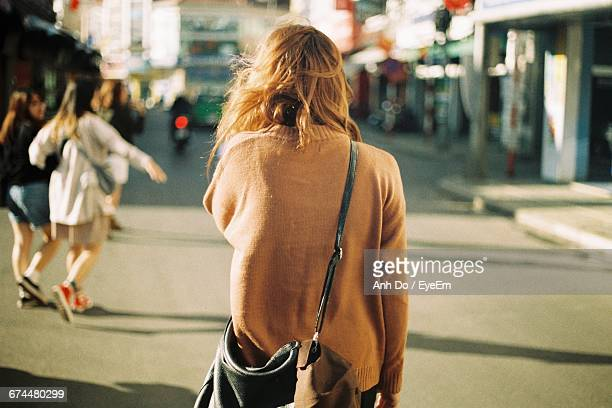 rear view of woman walking in the city - mensch im hintergrund stock-fotos und bilder