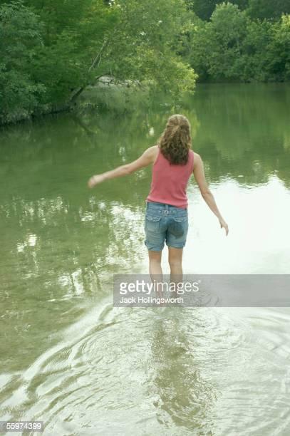 Rear view of woman walking in water
