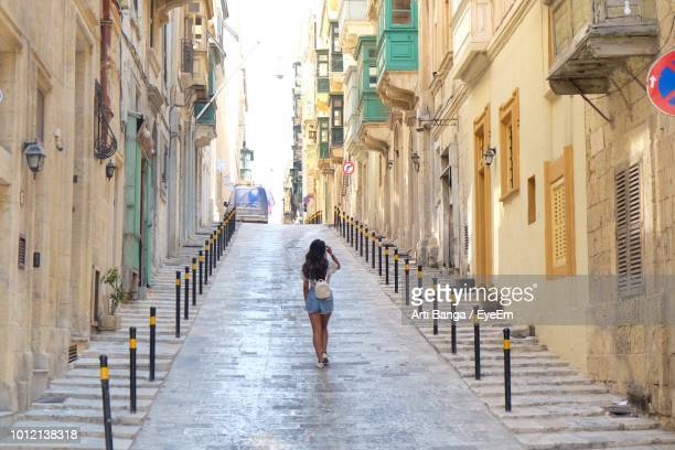 rear view of woman walking on alley amidst buildings in city - valletta stock pictures, royalty-free photos & images