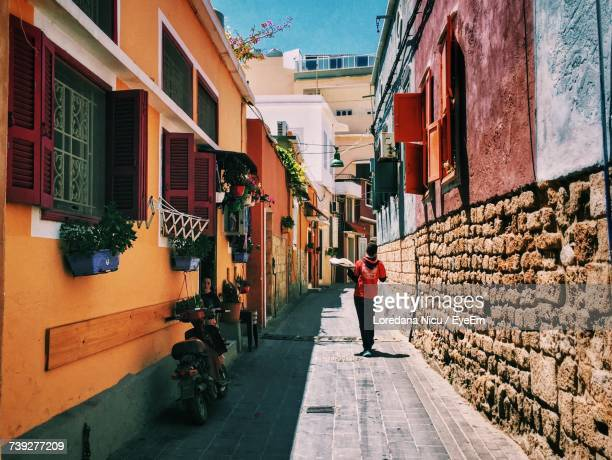 rear view of woman walking on alley in city - lebanon stock photos and pictures