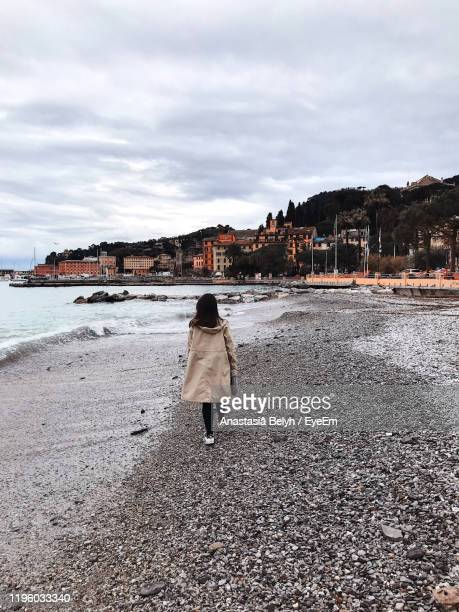 rear view of woman walking on beach - one young woman only stock pictures, royalty-free photos & images