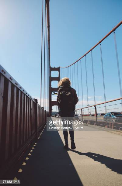 rear view of woman walking on bridge against blue sky - bortes foto e immagini stock