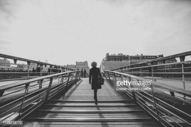 rear view of woman walking on bridge in city - bortes stock pictures, royalty-free photos & images