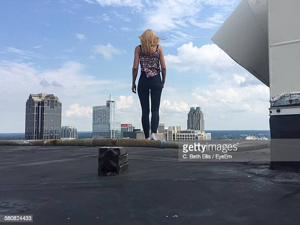 rear view of woman walking on building terrace - raleigh north carolina stock pictures, royalty-free photos & images