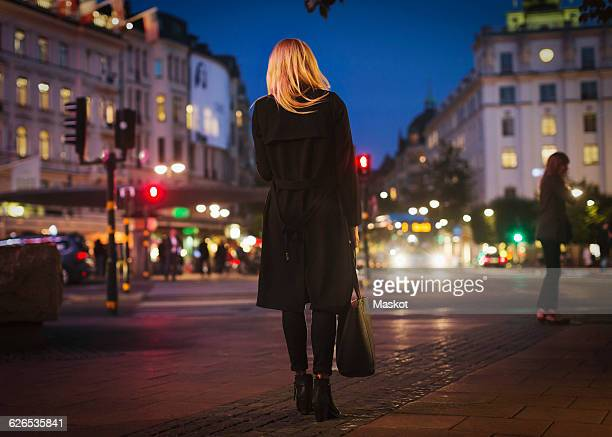 rear view of woman walking on city street at night - coat ストックフォトと画像