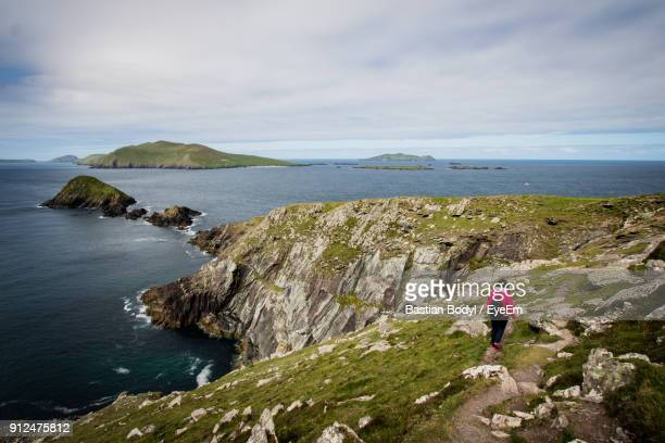 Rear View Of Woman Walking On Cliff By Sea Against Cloudy Sky
