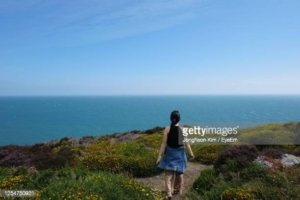 rear view of woman walking on cliff by sea against sky - cliff stock pictures, royalty-free photos & images
