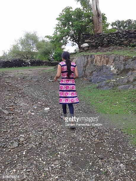rear view of woman walking on dirt road - salwar kameez stock pictures, royalty-free photos & images