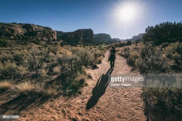 rear view of woman walking on field at colorado national monument - colorado national monument stock-fotos und bilder