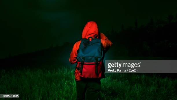 rear view of woman walking on field at night - capucha fotografías e imágenes de stock