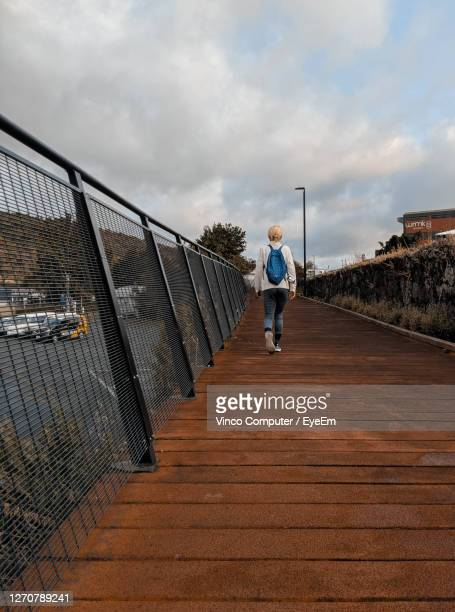 rear view of woman walking on footbridge against sky - whangarei heads stock pictures, royalty-free photos & images