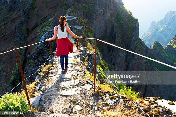 rear view of woman walking on footbridge - lareira stock pictures, royalty-free photos & images