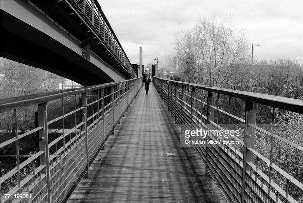 Rear View Of Woman Walking On Footbridge