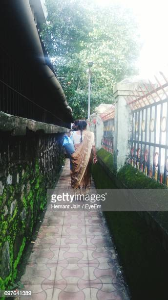 Rear View Of Woman Walking On Footpath Amidst Fence