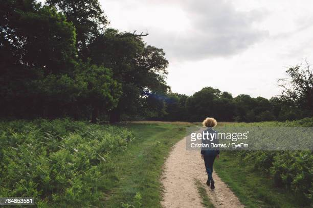 Rear View Of Woman Walking On Footpath Amidst Plants