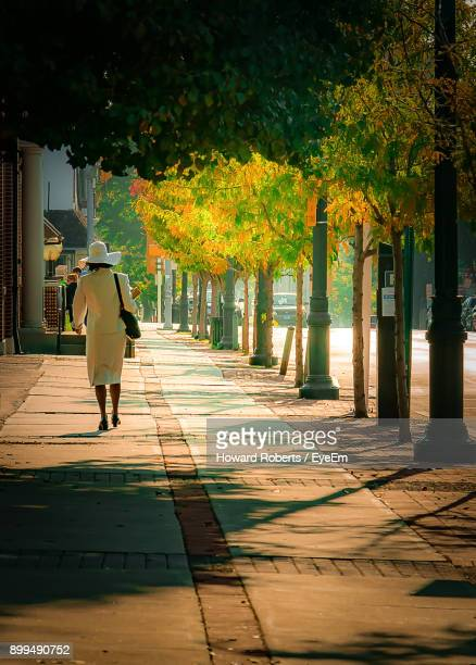 rear view of woman walking on footpath by trees - montgomery county pennsylvania stock pictures, royalty-free photos & images