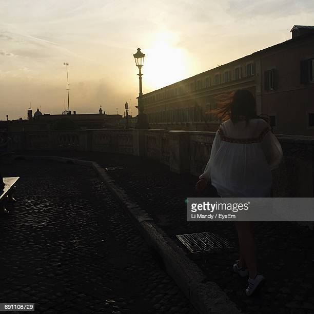 rear view of woman walking on footpath during sunset - one young woman only stock pictures, royalty-free photos & images