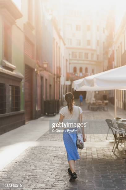 rear view of woman walking on footpath in city - grand canary stock pictures, royalty-free photos & images