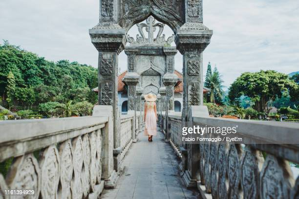 rear view of woman walking on footpath - denpasar stock pictures, royalty-free photos & images