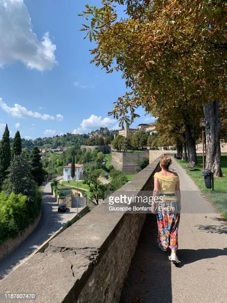 rear view of woman walking on footpath - bergamo stock pictures, royalty-free photos & images