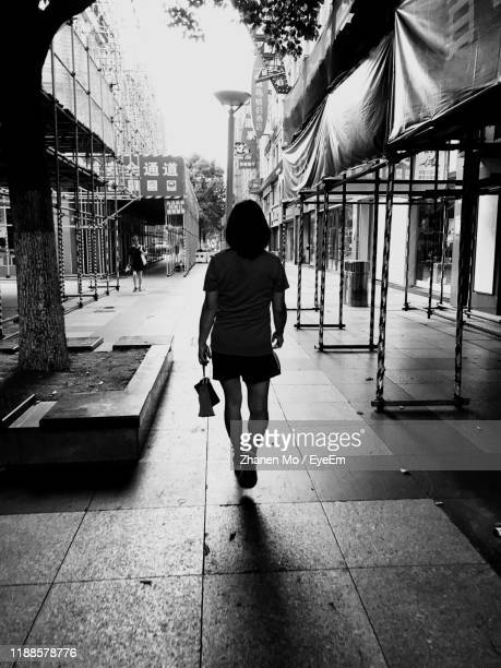 rear view of woman walking on footpath - wuhan stock pictures, royalty-free photos & images