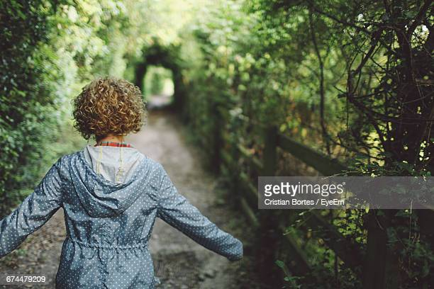 rear view of woman walking on footpath - bortes imagens e fotografias de stock